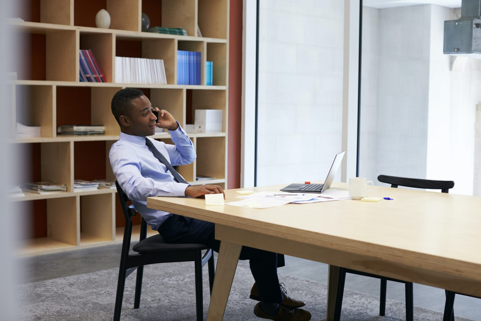 Young black businessman using smartphone in the boardroom